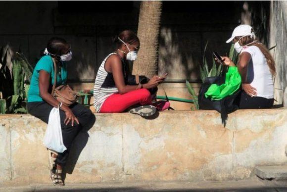 Las personas usan sus teléfonos móviles con máscaras protectoras en medio de las preocupaciones sobre la propagación del brote de coronavirus, en La Habana, Cuba, el 19 de marzo de 2020. Foto: Reuters / Stringer