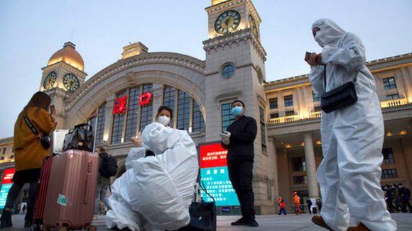 Pasajeros con trajes de protección contra la propagación del coronavirus esperan en el exterior de la estación de tren Hankou antes de la reanudación del servicio, en Wuhan, en la provincia de Hubei, en el centro de China, el 8 de abril de 2020. Foto: AP.