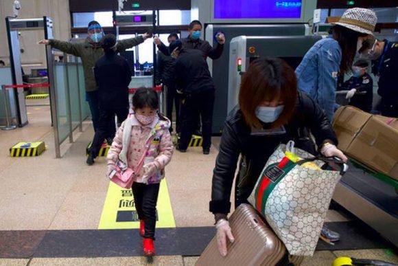 Pasajeros con mascarillas para protegerse del coronavirus pasan controles de seguridad en la estación de tren de Hankou luego de la reanudación del servicio, en Wuhan, en la provincia de Hubei, en el centro de China, el 8 de abril de 2020. Foto: AP.