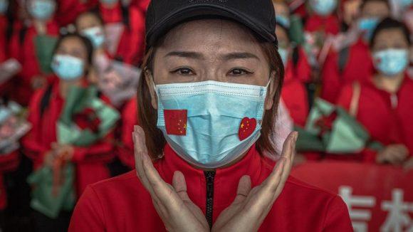 Una profesional sanitaria del primer hospital de Bethune de la Universidad de Jilin, emocionada en el aeropuerto, a la espera de abandonar Wuhan tras el fin del confinamiento (ROMAN PILIPEY / EFE)