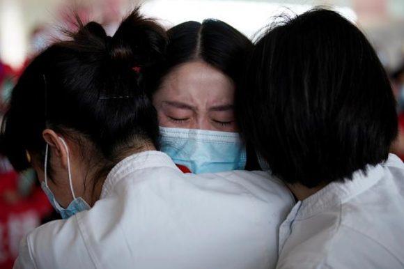 Personal sanitario se abraza en el aeropuerto internacional de Wuhan. Foto: Reuters.