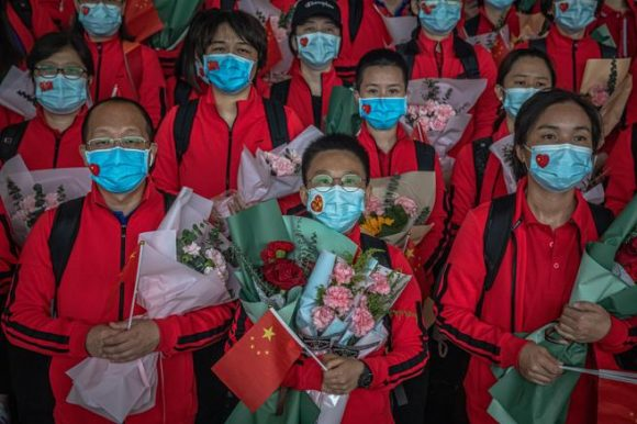 Personal sanitario del The First Bethune Hospital de la Universidad de Jilin, durante una ceremonia en el aeropuerto, se disponen a abandonar Wuhan (ROMAN PILIPEY / EFE)