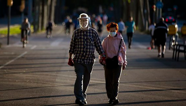 Una pareja usa mascarillas para protegerse del coronavirus en Barcelona, España, el 13 de mayo de 2020. / Foto: Reuters.