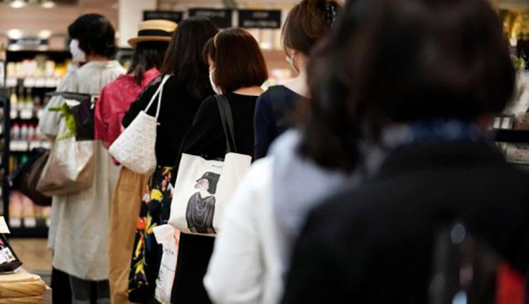 Clientes manteniendo distancia entre ellas mientras esperan en fila para pagar en una sección de alimentación de los grandes almacenes Matsuya Ginza, que reabría parcialmente el lunes, 25 de mayo de 2020, en Tokio. / Foto: AP.