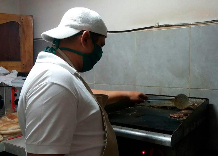 El lunchero Osmany Lugo Báez en plena faena productiva elaborando hamburguesas