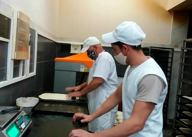 Los panaderos Luis Enrique Martínez Piquero, maestro elaborador y su ayudante Arturo Borrego Moreno. Ellos se encargan de los panes y las pizzas